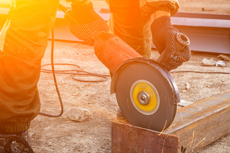 Close up of a strong  man welder in brown uniform,  welders leathers, grinder metal an angle grinder  at the construction site, orange sparks fly to the sides