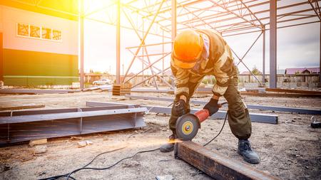 Un soldador de hombre fuerte en uniforme marrón, un casco de construcción y cueros de soldador, amoladora de metal y amoladora angular en el sitio de construcción, chispas naranjas vuelan a los lados Foto de archivo