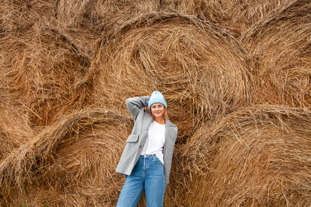 Pretty fresh darkhaired young woman walking outdoors in the sun against the background of haystacks and wearing a coat, knitting hat, jeans.Concept of autumn  holidays at village  and live style
