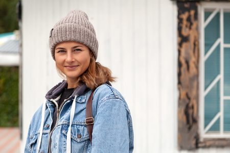 Portrait young woman in blue jeans coat, knitting hat, jeans against the background of the old lighthouse . Concept of autumn  holidays at village  and live style