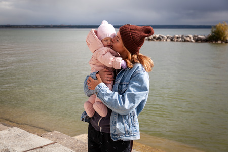 Atmospheric lifestyle photo of young beautiful  darkhaired woman  in knitting hat, in a leather jacket  and black trousers walks and plays with his little daughter  baby  in the background sea  in sunny autumn day