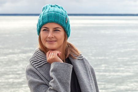 Romantic young woman on blue natural sea background outdoors. Portrait of a beautiful young brunette woman on the beach, she has long hair and wears coat and knitting hat