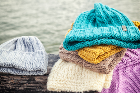 Beautiful background knitting winter blue and yellow a lot hat. Crochet hook handmade. Close-up of knitted hats of blue, yellow, pink and white