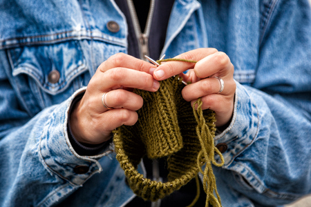 Close up of a young  married woman dressed in trendy denim coat knitting a green hat with knitting needles on a summer day. Freelance creative working and living concept