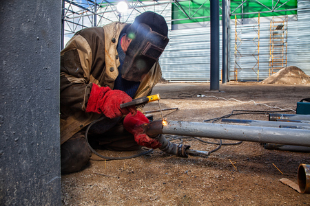 A builder welder in brown working clothes welds a metal product with arc  welding machine in the factory, a lots of tools and constraction, bright lights and sparks