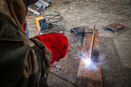 Close up of a builder welder in brown working clothes welds a metal product with arc welding machine in the factory, a lots of tools and constraction, bright lights and sparks