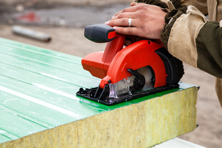 A young man welder in a working overall and working gloves grinds a sandwich panels with a angle grinder in the constraction side