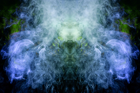 Fantasy print for clothes: t-shirts, sweatshirts.  Colorful blue and green smoke in the form of a skull, monster, dragon on a black isolated background. Background from the smoke of vape Foto de archivo