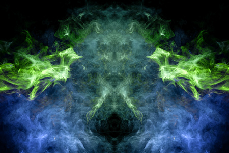 Fantasy print for clothes: t-shirts, sweatshirts. Colorful blue and green smoke in the form of a skull, monster, dragon on a black isolated background. Background from the smoke of vape Stock Photo