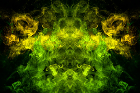 Fantasy print for clothes: t-shirts, sweatshirts. Thick colorful smoke of yellow, green colors smoke in the form of a skull, monster, dragon on a black isolated background. Background from the smoke of vape Foto de archivo