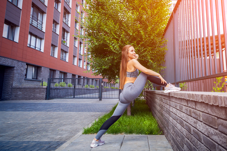 Young woman gymnast with a slim figure in sportswear doing stretching on a city street on a warm summer day. Stretching in the open air Stockfoto