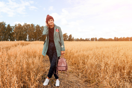 Portrait female student on field background. Beautiful modern  young woman wearing pink knitting hat  smile, look at the camera and enjoy autumn sunny day. Standard-Bild