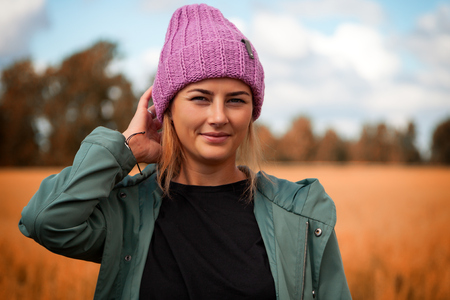 Portrait female student on field background. Beautiful modern  young woman wearing pink knitting hat  smile, look at the camera and enjoy autumn sunny day. Stock Photo