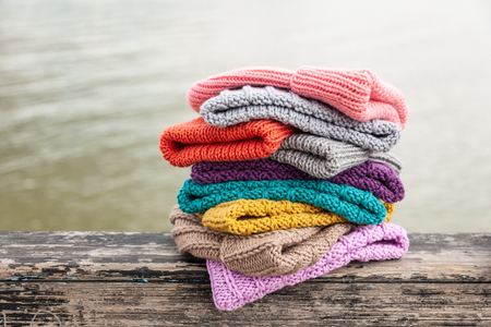 Rows of  colorful knitted hats for sale on  natural background. A colourful collection of bobble hats lined up Stock Photo