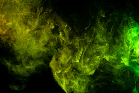 Textural background for creativity. Cloud of green and yellow smoke on a black isolated background. Background from the smoke of vape