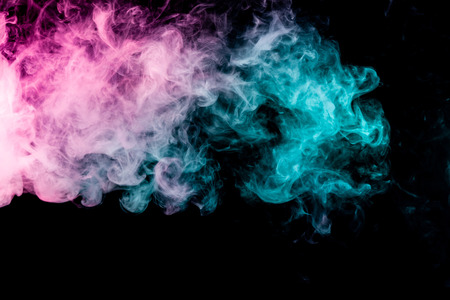 Textural background for creativity . Dense multicolored smoke of   blue and pink colors on a black isolated background. Background of smoke vape Stock Photo