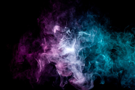 Textural background for creativity. Colorful pink and blue smoke  on a black isolated background. Background from the smoke of vape