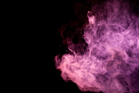 Textural background for creativity . Dense multicolored smoke of   red and pink colors on a black isolated background. Background of smoke vape