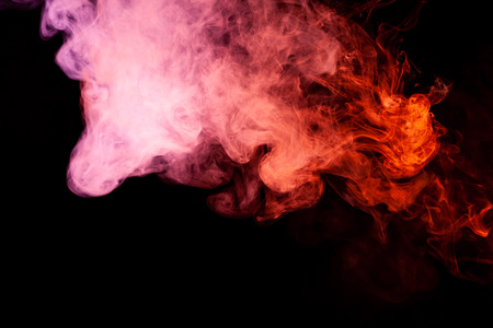 Textural background for creativity. Colorful pink and red smoke  on a black isolated background. Background from the smoke of vape Stock Photo