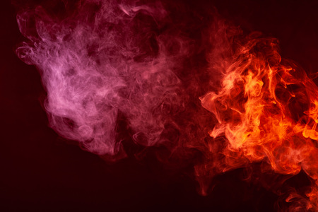 Textural background for creativity. Cloud of red and pink smoke on a black isolated background. Background from the smoke of vape