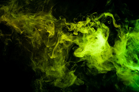 Textural background for creativity. Green and yellow cloud of smoke of  black isolated background. Background from the smoke of vape Stock Photo