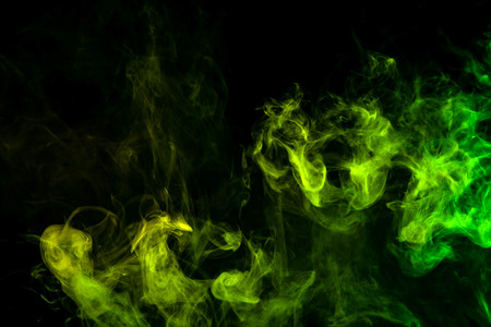 Textural background for creativity . Dense multicolored smoke of   green and yellow colors on a black isolated background. Background of smoke vape