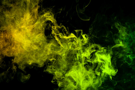 Textural background for creativity. Colorful green and yellow smoke  on a black isolated background. Background from the smoke of vape