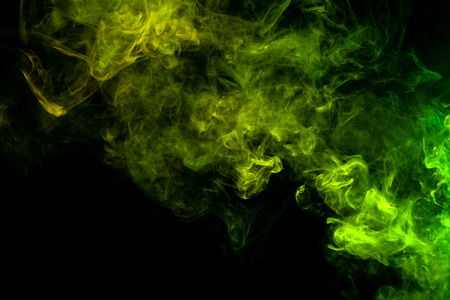 Textural background for creativity. Thick colorful smoke of green, yellow on a black isolated background. Background from the smoke of vape