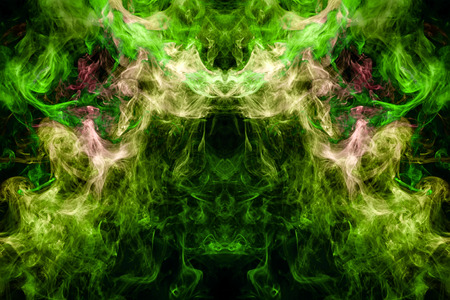Dense multicolored smoke of   green, yellow and pink colors in the form of a skull, monster, dragon on a black isolated background. Background of smoke vape. Mocap for cool t-shirts