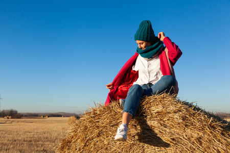 Portrait of a beautiful young model in  blue knitted hat  and warm clothes  have fun,  sitting on haystacks in  sunny autumn day . Autumn warm photo. Woman smiling and look away, joyful cheerful mood. Foto de archivo