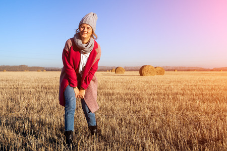Portrait female student on field background. Beautiful modern  young woman wearing gray knitting hat  and pink coat smile, look at the camera and enjoy autumn sunny day. Stockfoto
