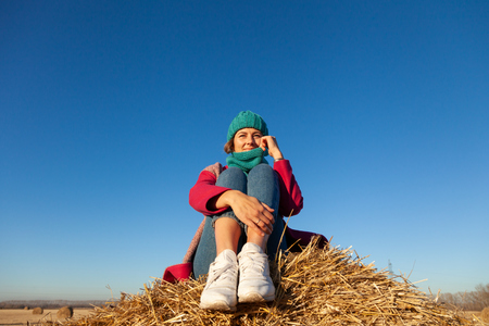 Young attractive lady in blue knitting hat and pink coat sitting on haystack. Smiling beautiful hipster happy woman on field, wearing stylish clothes. Autumn trend, urban stydent style.