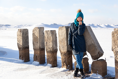 A young woman in a blue knitting hat,  black coat  enjoys winter nature, walking on the frozen sea at the north pole around blue sky in winter frosty day. The concept of livestyle and outdoor recreation in winter
