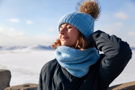 Portrait beauty woman model on winter background. Beautiful modern  young woman wearing blue knitting hat  warm hands, smile, look at camera on a walk on the frozen sea in winter Stockfoto