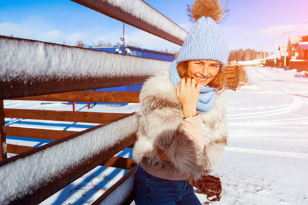 The concept of livestyle  outdoor in winter. A young woman student in a blue knitting hat,a white fur coat  smiles, looks into the camera and walks through the winter village, in the background fences and houses in the snow on a warm winter day