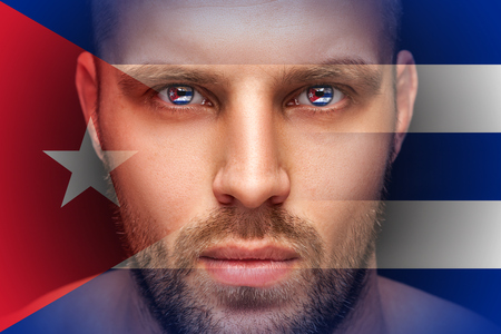 A portrait of a young serious man, in whose eyes are reflected the national flags  Cuba, against an isolated black background and flag Imagens