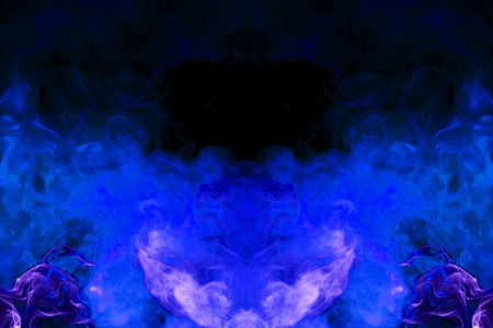 Dense multicolored smoke of   blue and purple colors in the form of a skull, monster, dragon on a black isolated background. Background of smoke vape. Stock Photo