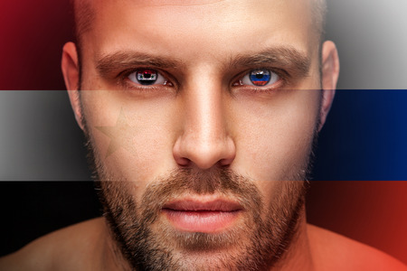 Portrait of a serious young man, in whose eyes the reflected national flag of Syria and Russia, against an isolated black background and flag