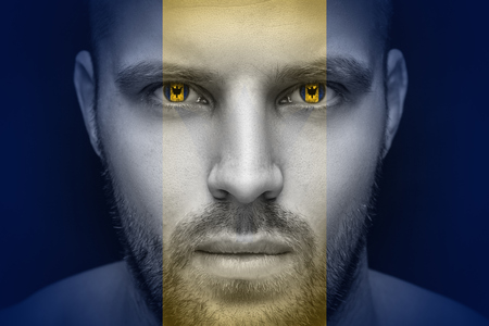 Portrait of a young serious man, in whose eyes the reflected national flag of Barbados, against an isolated black background and flag