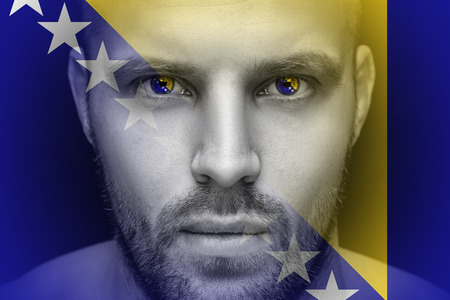 Portrait of a young serious man, in whose eyes the reflected national flag of Bosnia Herzegovina, against an isolated black background and flag Фото со стока