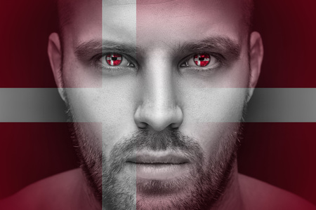 Portrait of a young serious man, in whose eyes the reflected national flag of Denmark, against an isolated black background and flag Stok Fotoğraf