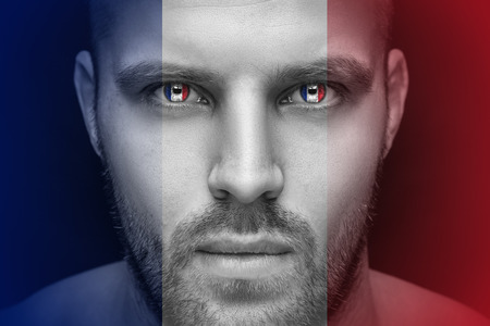 Portrait of a young serious man, in whose eyes the reflected national flag of France, against an isolated black background and flag