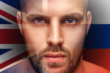 A portrait of a young serious man, in whose eyes are reflected the national flags of Russia and the United Kingdom, against an isolated black background and flag