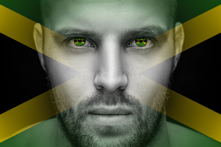 Portrait of a young serious man, in whose eyes the reflected national flag of Jamaica, against an isolated black background and flag Banque d'images