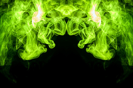 Fantasy print for clothes: t-shirts, sweatshirts.  Colorful green and yellow  smoke in the form of a skull, monster, dragon on a black isolated background. Background from the smoke of vape