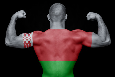 The back of a young sports man wearing a T-shirt with the national flag of Belarus on a black isolated background. The concept of national pride and patriotism Фото со стока