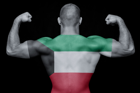 The back of a young athletic man wearing a T-shirt with the national flag of Kuwait on a black isolated background. The concept of national pride and patriotism