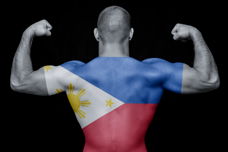 The back of a young athletic man wearing a T-shirt with the national flag of the Philippines on a black isolated background. The concept of national pride and patriotism