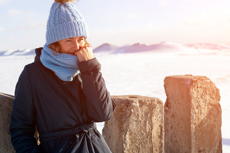 Portrait beauty woman model on winter background. Beautiful modern urban young woman wearing blue knitting hat  basks in cold weather on the background of the frozen sea Stock Photo