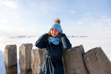 Fashion lifestyle portrait of young trendy woman dressed in warm stylish clothes  laughing and smiling in the  winter mountains.  portrait of joyful woman